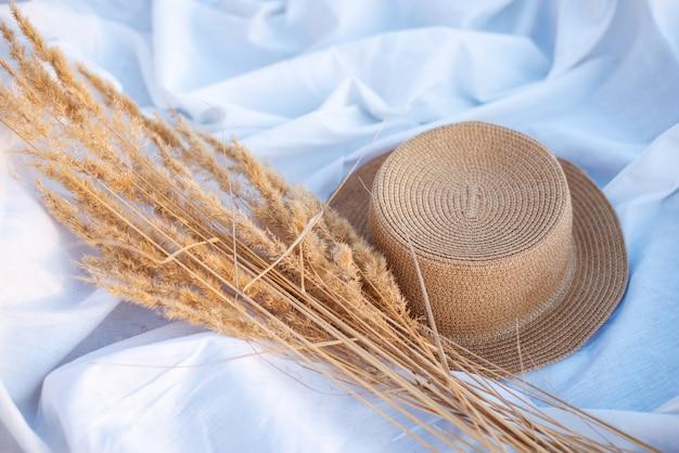 Flores secas de junco e um chapéu de palha em um lençol branco com raios quentes de sol