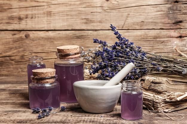 Flores secas de lavanda em um almofariz e pilão com frasco de óleo essencial de lavanda