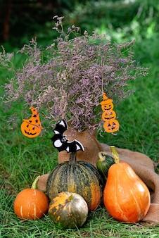 Flores secas e abóboras em serapilheira e grama verde com elementos de decoração de halloween