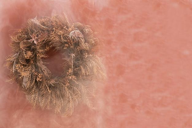 Flores secas e poluição na parede rosa