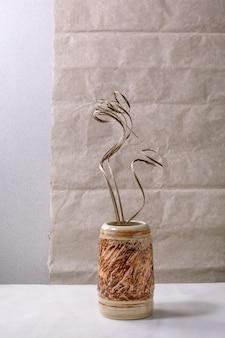 Flores secas e ramos de galhos em vaso de cerâmica marrom na mesa de mármore branco com parede cinza atrás. copie o espaço.