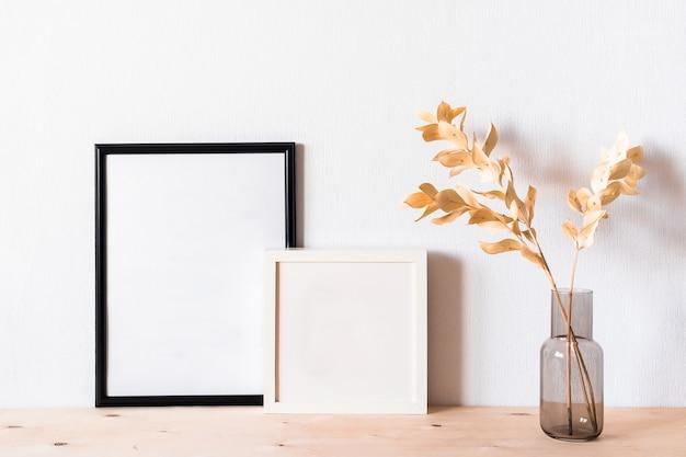 Flores secas e uma moldura de foto contra uma parede de luz
