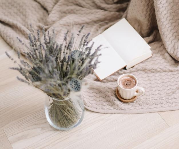 Flores secas e uma xícara de cappuccino com livro na vista superior do plano de fundo de madeira