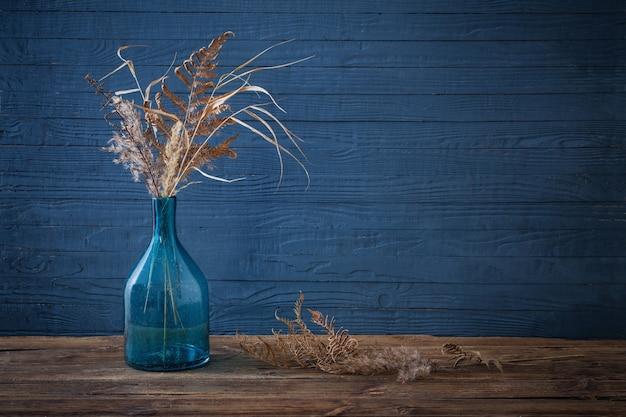 Flores secas em um vaso de vidro na mesa de madeira com fundo azul