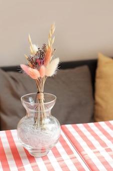 Flores secas em um vaso na mesa de café, toalha de mesa italiana em cima da mesa.