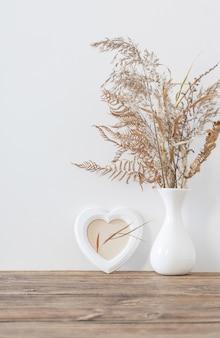 Flores secas em um vaso na mesa de madeira em branco