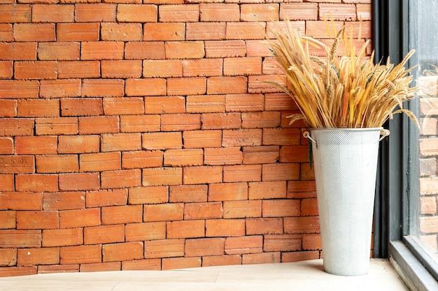 Flores secas em vaso com parede de tijolos