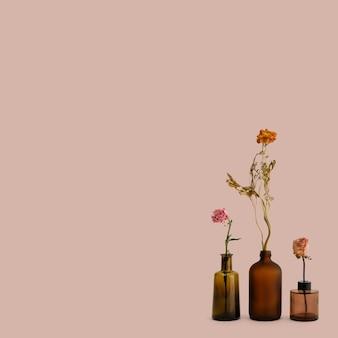 Flores secas em vasos de vidro marrom em um fundo rosa