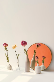 Flores secas em vasos mínimos perto de um espelho redondo