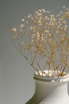 Flores secas, galhos secos de plantas em um vaso antigo branco na janela.