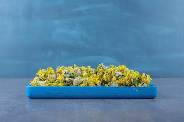Flores secas na bandeja de madeira azul sobre cinza.