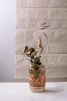 Flores secas, ramos de eucalipto e galhos em vaso de cerâmica marrom na mesa de mármore branco com parede cinza atrás. c