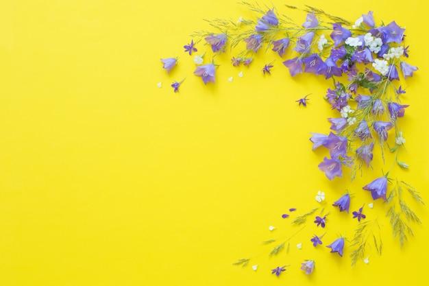 Flores silvestres azuis na superfície amarela
