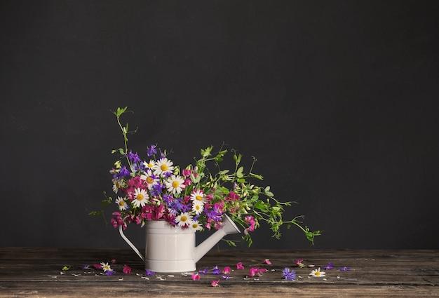 Flores silvestres de verão em regador na parede escura