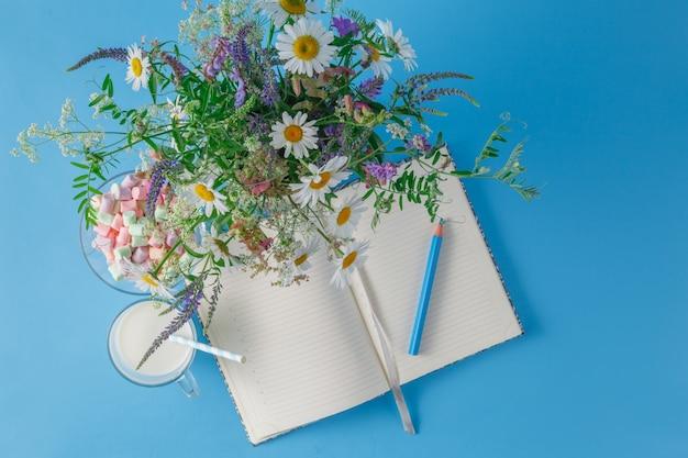 Flores silvestres e um bloco de notas em fundo azul liso