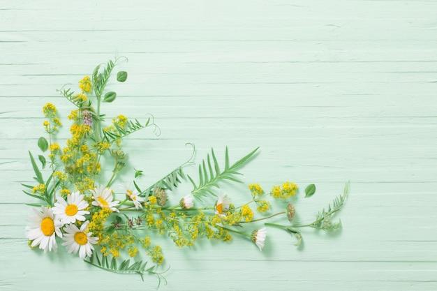Flores silvestres em fundo verde de madeira