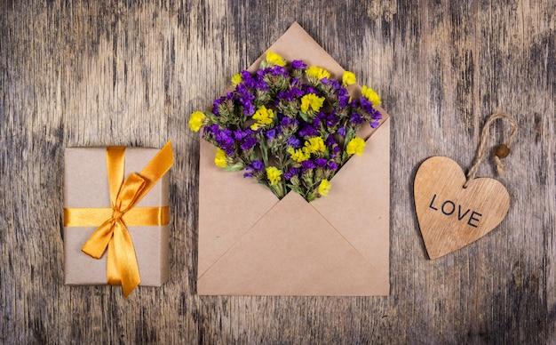Flores silvestres em um envelope, caixa com laço de ouro e coração