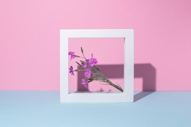 Flores silvestres em uma moldura quadrada branca, um pódio de apresentação em um fundo rosa-azulado.