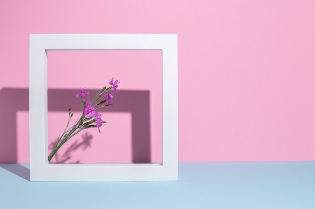 Flores silvestres lilases em uma moldura quadrada branca, um pódio de apresentação em um fundo rosa-azulado.