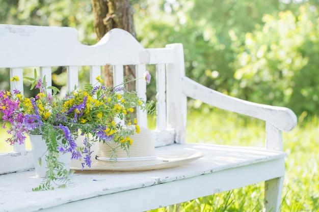 Flores silvestres no banco de madeira branco no jardim de verão