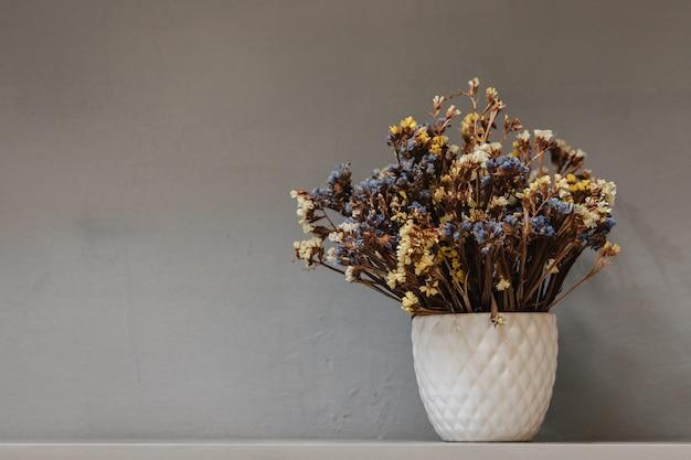 Flores silvestres secas em um vaso branco. buquê em um fundo cinza.