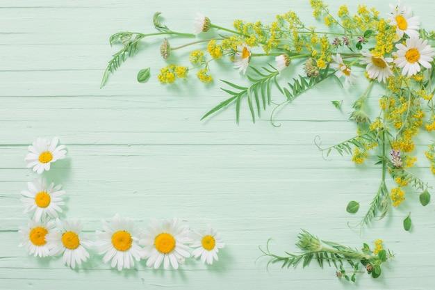 Flores silvestres sobre fundo verde de madeira