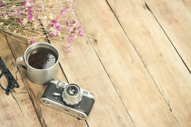 Flores silvestres, xícara de chá de metal, uma bússola e outros atributos para uma caminhada em uma superfície de madeira. conceito de caminhadas nas montanhas ou na floresta, turismo, descanso de barraca, acampamento. vista plana leiga, superior.