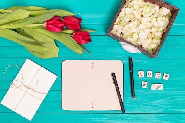 Flores tulipa vermelha; pétalas; cartão; caneta; e blocos de madeira sobre o pano de fundo verde