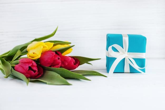 Flores tulipas e uma caixa com um presente. conceito de férias, birthd