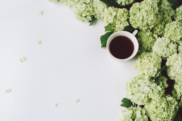 Flores verdes e copo amarelo com chá em um fundo branco