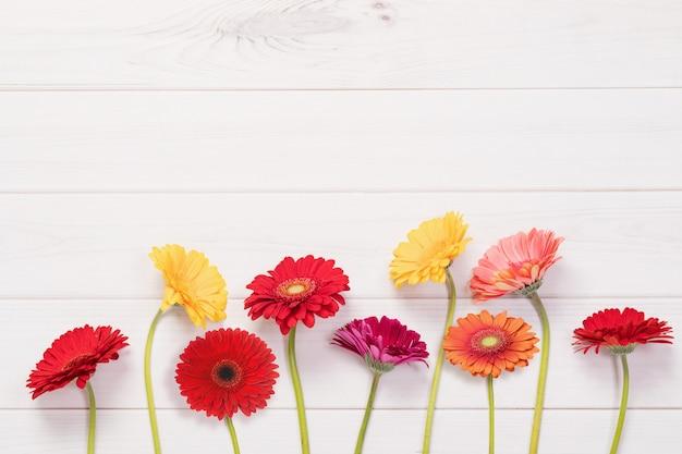 Flores vermelhas, amarelas do gerbera no fundo de madeira.