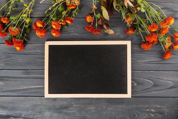 Flores vermelhas com lousa em branco na mesa de madeira
