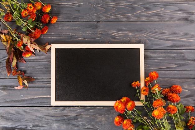 Flores vermelhas com lousa na mesa de madeira