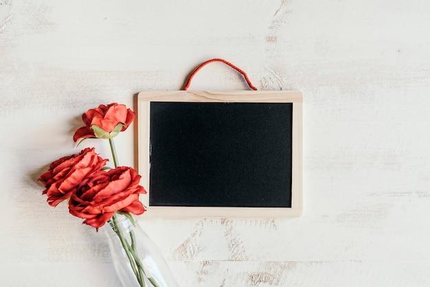 Flores vermelhas com quadro-negro