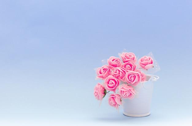 Flores vermelhas em um balde de brinquedo branco sobre um fundo azul ou roxo, flores para o feriado