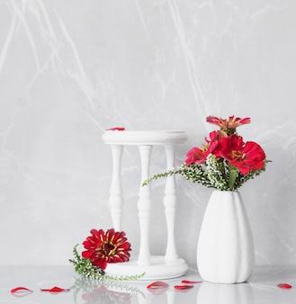 Flores vermelhas em um vaso branco e um suporte de madeira sobre um fundo de mármore cinza