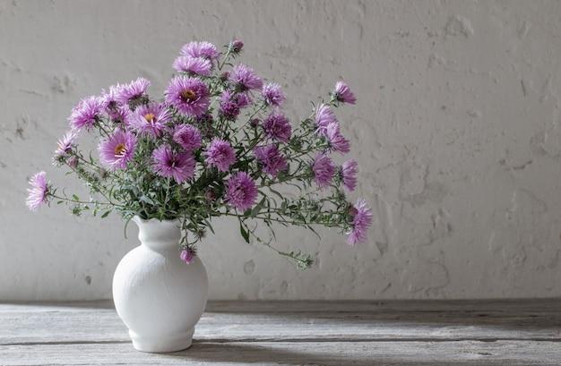 Flores violeta em um vaso branco na parede velha