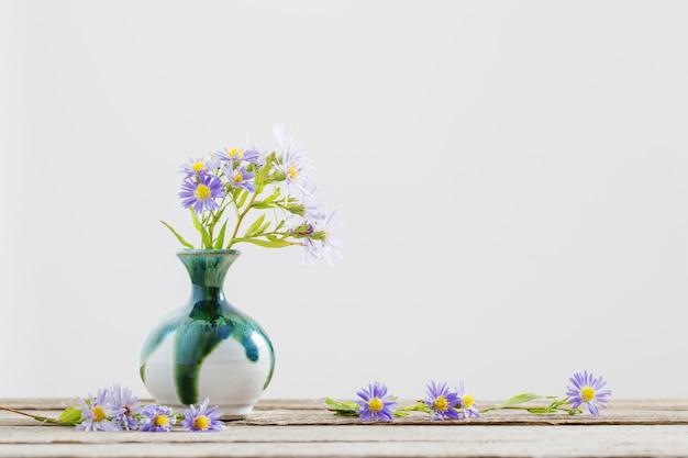 Flores violeta em um vaso na mesa de madeira