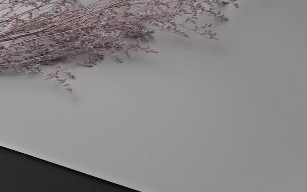Flores violetas secas e espessas planas sobre fundo cinza pastel.