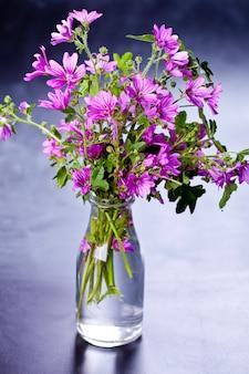 Flores violetas selvagens em garrafa de vidro