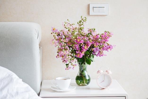Flores, xícara de café e despertador no quarto