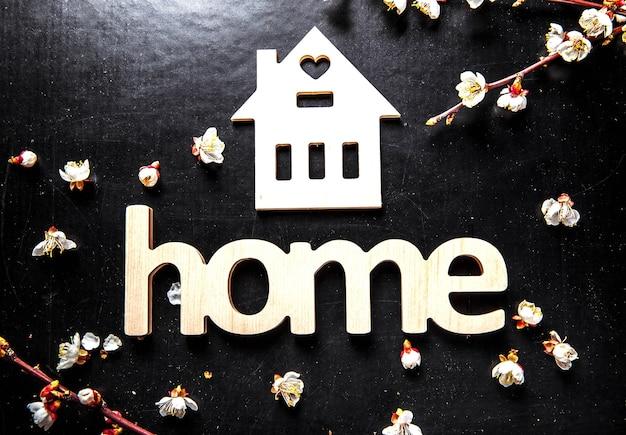 Floresça em um fundo preto e uma placa de madeira com a palavra casa