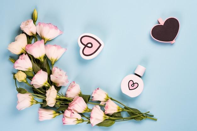 Florescendo eustoma rosa com coração parfume e placa de giz de madeira, configuração plana.