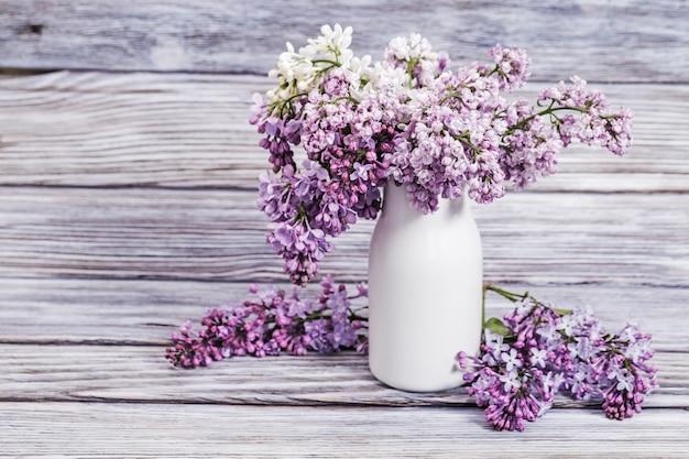 Florescendo flores lilás em vaso branco na madeira