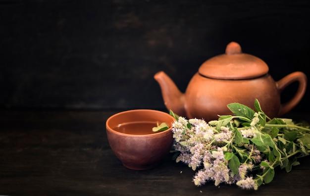 Florescendo grama com uma xícara de chá e um bule de chá em uma mesa de madeira escura com uma cópia do espaço