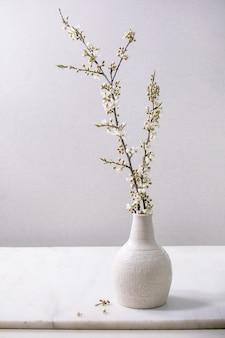 Florescendo ramos de cereja em vaso de porcelana branca artesanal na mesa de mármore branco. decoração de interiores de flores de primavera.
