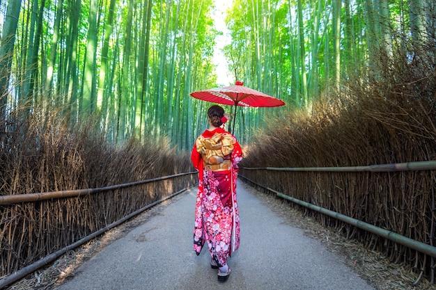 Floresta de bambu. mulher asiática vestindo quimono tradicional japonês na floresta de bambu em kyoto, japão.