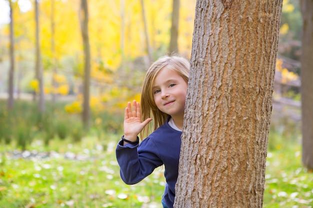 Floresta de outono com criança menina saudação mão no tronco de árvore