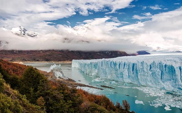 Floresta do outono, nuvens dramáticas e a geleira de perito moreno no lago argentino, argentina. américa do sul