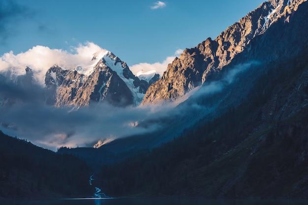 Floresta fantasmagórica perto do lago de montanha no início da manhã.